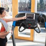 HZ19_LIFESTYLE_7_0AT-female_treadmill_grabbing-tablet_back-angle_lores-scaled