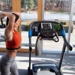 HZ19_LIFESTYLE_7_0AT-female_treadmill_lifting-weight-looking-at-tablet_back_lores-scaled